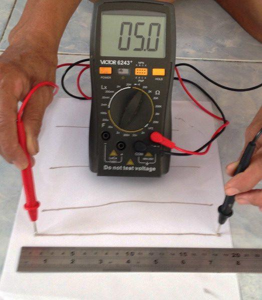 Проверка мультиметром электропроводимости полосы клея на бумаге