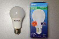 Электролампа и её упаковка, на которой указано её энергопотребление, в Вт